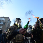 Masked and hooded protesters holding Molotov Cocktails seen duri
